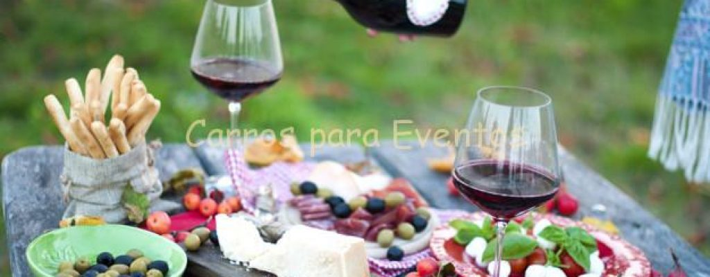 Italian picnic with red wine, parmesan, ham and olives. Lunch in the open air. Traditional snacks. A man pours a glass of wine. Copy space,
